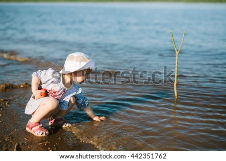 A cute little girl on the river bank in a warm sunny summer day.