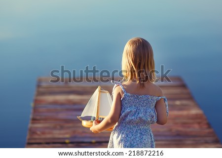 A cute little girl sitting on the pontoon bridge on the river with a toy ship in hands in a warm sunny summer day. Water and boat. - stock photo
