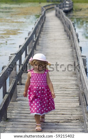 A cute little girl takes a stroll on the boardwalk through the marsh. - stock photo