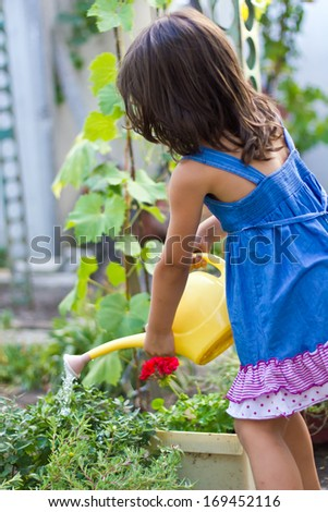 A cute little girl wearing dress watering in the garden. - stock photo