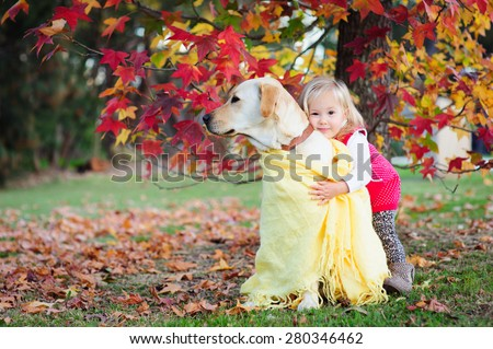 A cute little toddler girl giving a hug to her dog, a yellow labrador in a park with autumn trees in the background - stock photo