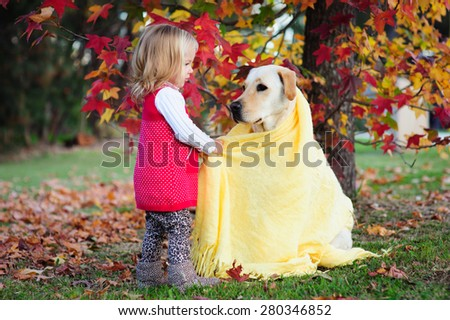 A cute little toddler girl playing with her dog, a yellow labrador in the park with autumn trees in the background - stock photo