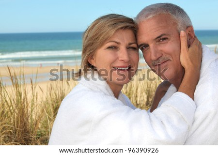 A cute middle age couple at the beach. - stock photo