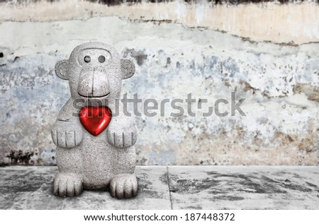 A cute monkey with a big red heart, squatting by a concrete pavement.  - stock photo