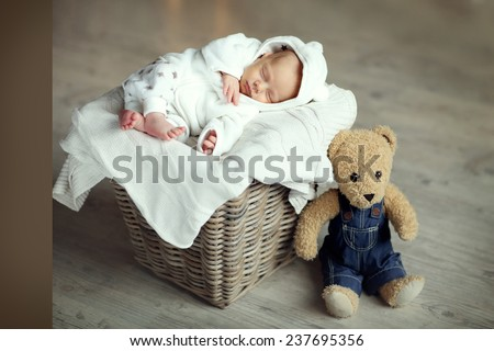 A cute newborn baby in a white suit sleeping in a wicker basket with a teddy bear sitting by on the floor. - stock photo