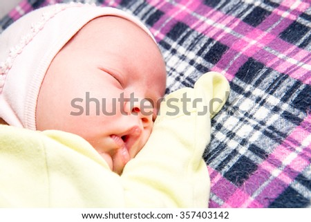 A cute newborn little baby girl sleeping. Use it for a child, parenting or love concept. - stock photo