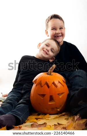 A cute photograph of a two boys and her Halloween pumpkin - stock photo