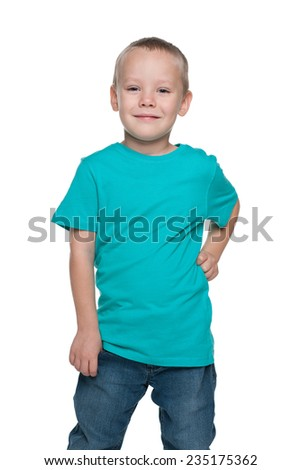 A cute preschool boy in a blue shirt is standing on the white background - stock photo