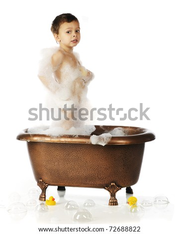 A cute preschool boy standing in a copper, claw-foot bathtub while covered with soap suds.  Isolated on white. - stock photo