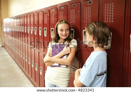A cute school girl talking to a boy outside her locker.  Lockers are textured.  May appear as noise or artifacts at 100%.