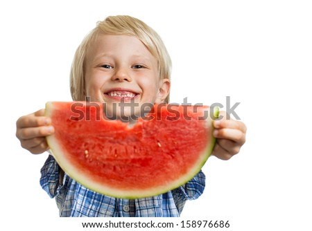 A cute smiling boy holding out and peeking through a bite in a slice water melon. Isolated on white.