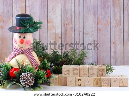 A cute snowman decoration with lamp inside is surrounded by holly, pine, pine cones and Christmas decorations. Merry Christmas message in letter blocks with copy space upper right. Rustic background - stock photo