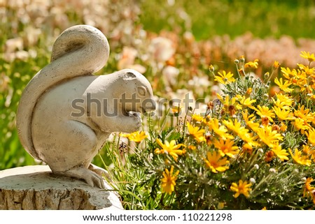 A Cute Stone Chipmunk Statue Made of Stone in a Yard Setting With Flowers