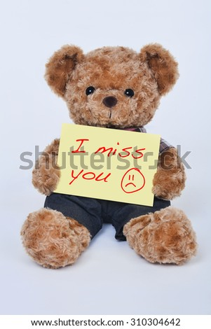 A cute teddy bear holding a yellow sign that says I miss you isolated on a white background - stock photo