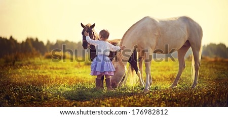 A cute white girl in jockey boots caressing her little pony in the field on a sunny summer day  - stock photo