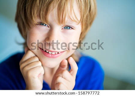 A cute white happy smiling boy with blue eyes close-up - stock photo