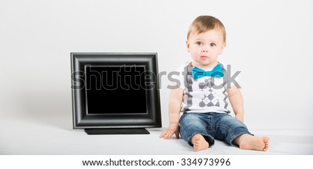 a cute 1 year old baby sits next to a blank black picture frame in a white studio setting. The boy has a confused expression. He is dressed in t-shirt, jeans, suspenders and blue bow tie - stock photo