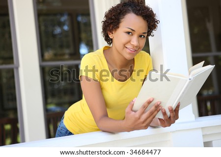A cute young african woman on porch at home reading a book