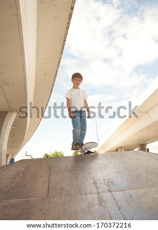 a cute young boy at a local skate park - stock photo