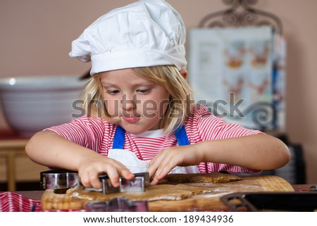 A cute young boy is concentrating while he is baking gingerbread cookies - stock photo