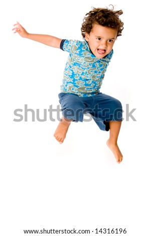 A cute young boy jumping in the air on white background