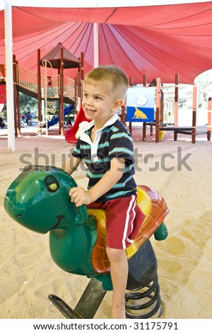 A cute young boy playing on a rocking horse in a park.