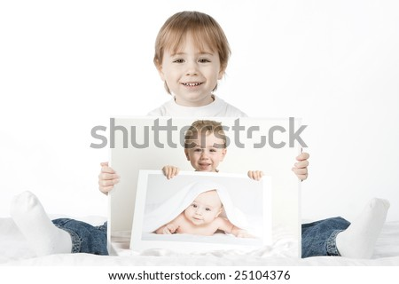 A cute young boy, sits on the floor, holding baby photographs of himself. The photographs are arranged such that the boy is holding a photo of his younger self, holding a photo of his baby self - stock photo