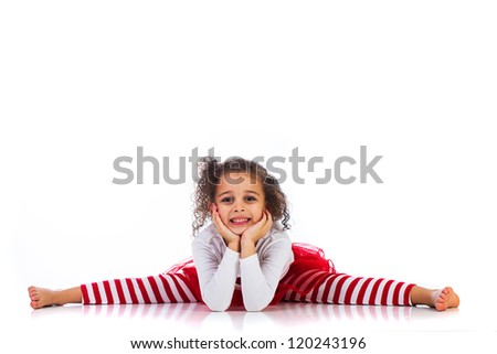A cute young girl doing the splits and resting her chin on her hands. - stock photo
