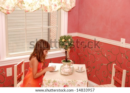 A cute young girl having tea in her bedroom - stock photo