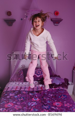 A cute young girl jumping on her bed - stock photo