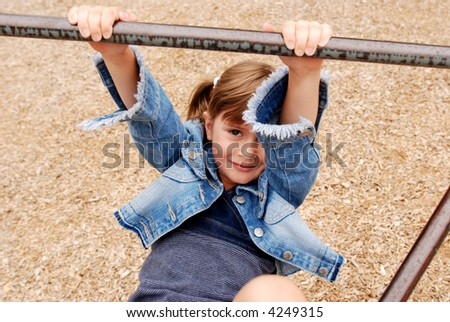 A cute young girl playing on the monkey bars - stock photo