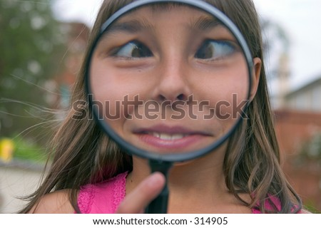 a cute young girl playing with a toy magnifying glass
