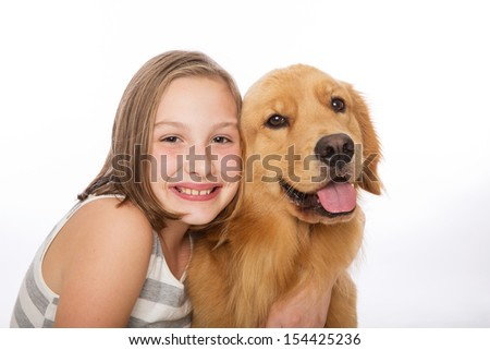A cute young girl sits with her pretty golden retriever dog
