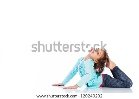 A cute young girl touching the back of her head with her feet. - stock photo