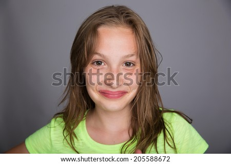 A cute young girl with a smirk on her face - stock photo