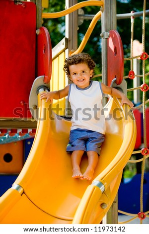 A cute young kid playing on a slide in a park - stock photo