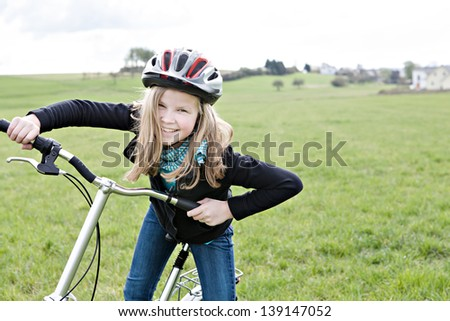 A cycling girl in front of rural landscape - stock photo