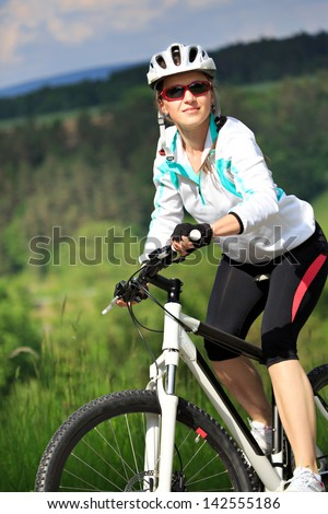 A cycling woman in front of rural landscape