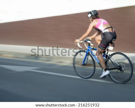A cycling woman on a triathlon competition following an arrow, photo sweep - stock photo