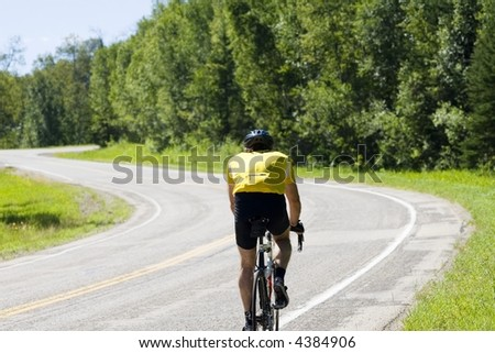 A cyclist climbs a hill in a bicycle race.