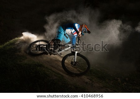A cyclist on a mountain bike with dusty aggressive turns. Downhill riding at dark night. Bicyclist on a bicycle. - stock photo