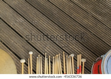 A cymbal, a red snare drum and a variety of different drumsticks on rough wood - stock photo