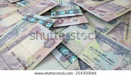 A 3D rendering of a macro close-up view of a messy scattered pile of dirham banknotes - stock photo