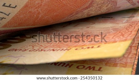 A 3D rendering of a  macro close-up view showing the detail in between two separated south african rand banknotes - stock photo