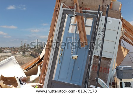 A damaged blue front door is all that is left after an EF5 tornado paid a visit to this home in Joplin, Missouri in May of 2011. - stock photo