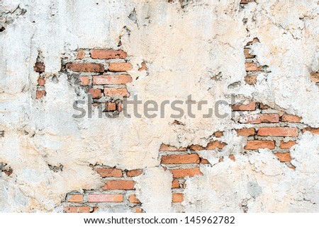 A damaged red clay brick wall with blank space for text as textural background. - stock photo