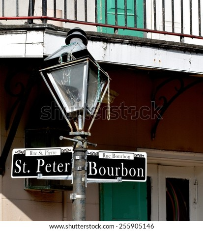 A damaged street lamp with Mardi Gras beads on the corner of Bourbon and St. Peter Streets in the New Orleans French Quarter.
