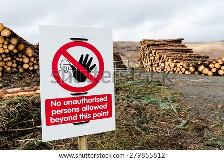 A danger and warning sign at site of timber harvest with stacks of logs awaiting collection from site. - stock photo