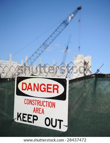 """A """"Danger, Construction Area, Keep Out"""" sign posted on a chain link fence.  The booms of cranes and a partially constructed building visible behind the fence. - stock photo"""