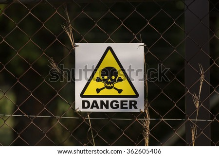 A danger sign with skull and bones on a chain-link wire fence - stock photo